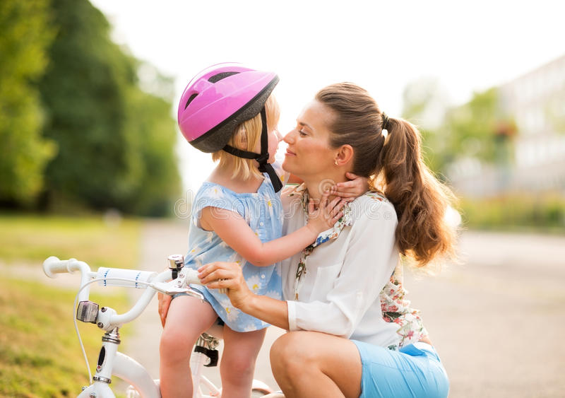 Eskimo kisses between a proud mother and daughter stock images