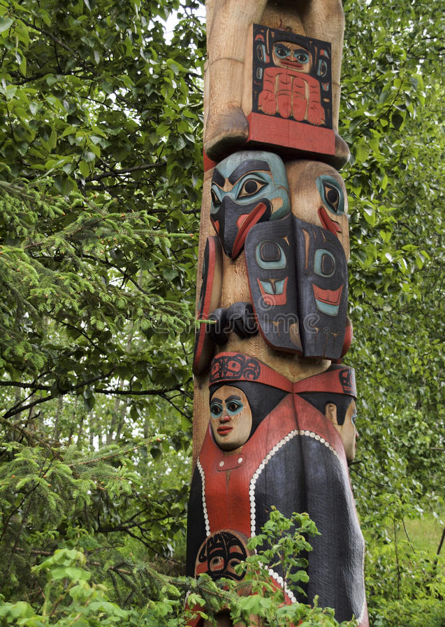Eskimo totem pole. Traditional Eskimo totem pole with leafy green background, Anchorage, Alaska, America stock image