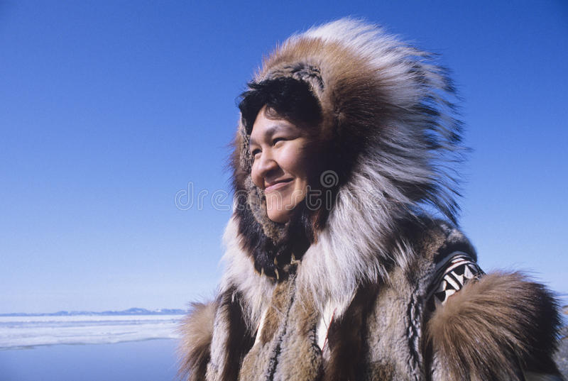 Eskimo Woman In Traditional Clothing. Smiling Eskimo woman wearing traditional clothing in wind against clear blue sky royalty free stock photos
