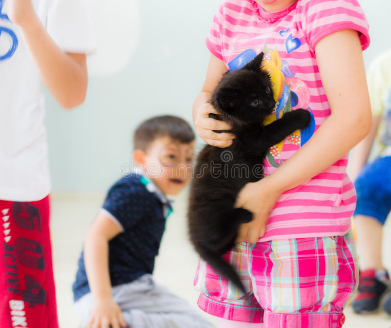 Eskisehir, Turkey - May 05, 2017: Preschool little girl holding a black kitten in her hands in a classroom. royalty free stock images