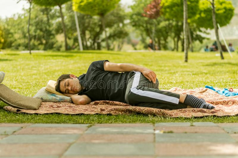 Young man in black clothings sleeping on grasses in a public park. Eskisehir, Turkey - May 24, 2015: Young man lying and sleeping on green grass in a picnic area royalty free stock images