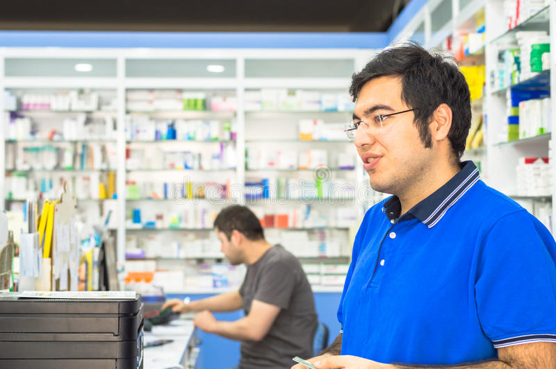 Eskisehir Turkiet - Juni 14, 2017: Stående av ett ungt manligt apotekareanseende på räknaren i apotek arkivbild