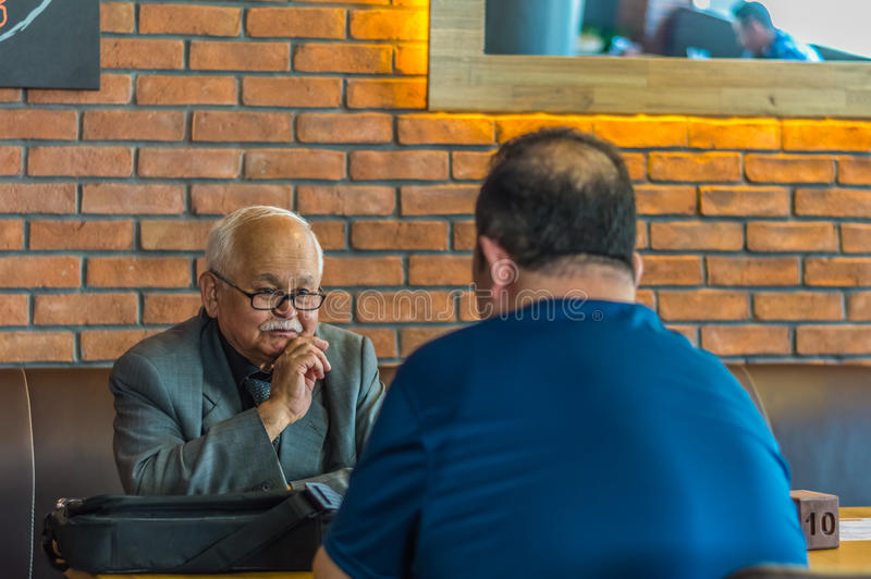 Eskisehir, Turquía - 19 de abril de 2017: Viejo hombre con las lentes que llevan el traje que se sienta en una tabla del café imágenes de archivo libres de regalías