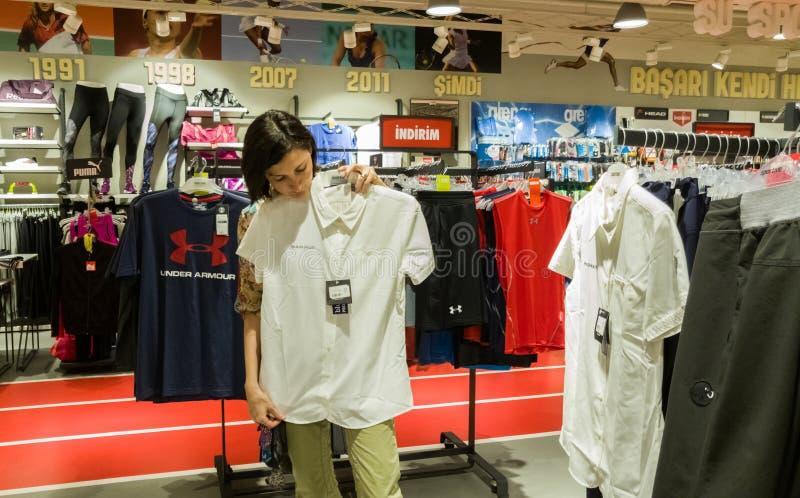 Eskisehir, Turquía - 11 de agosto de 2017: La mujer joven que mira una ropa de los deportes en los deportes hace compras en Eskis fotografía de archivo