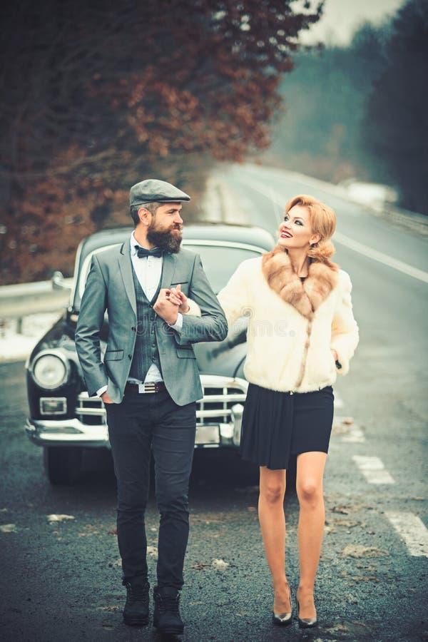 : Eskortenkonzept mit b?rtigem Fahrer und Luxusm?dchen im Retro- Auto stockbild