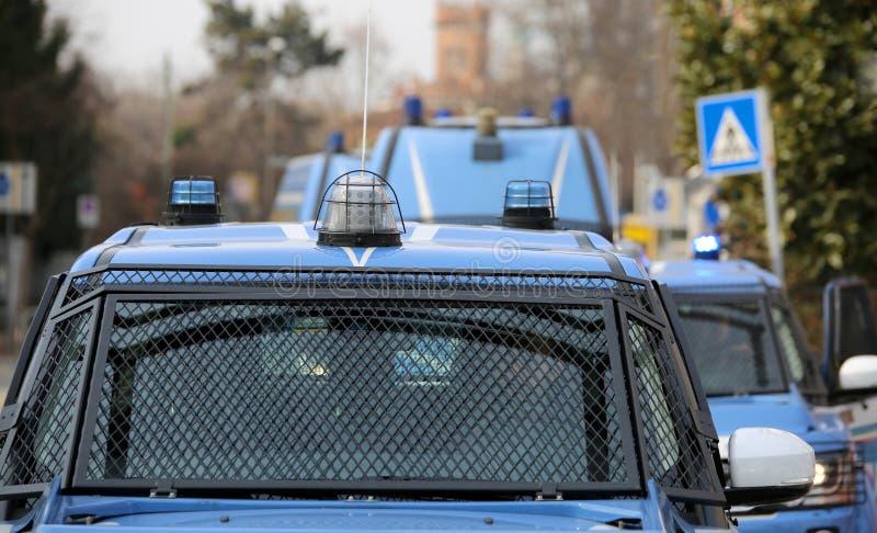 Eskortera med flera polisbilar och pansarbilar på patrull t royaltyfri fotografi