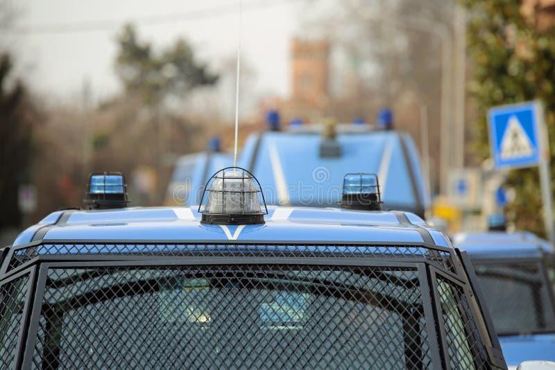 Eskortera med flera polisbilar och pansarbilar på patrull t arkivbild
