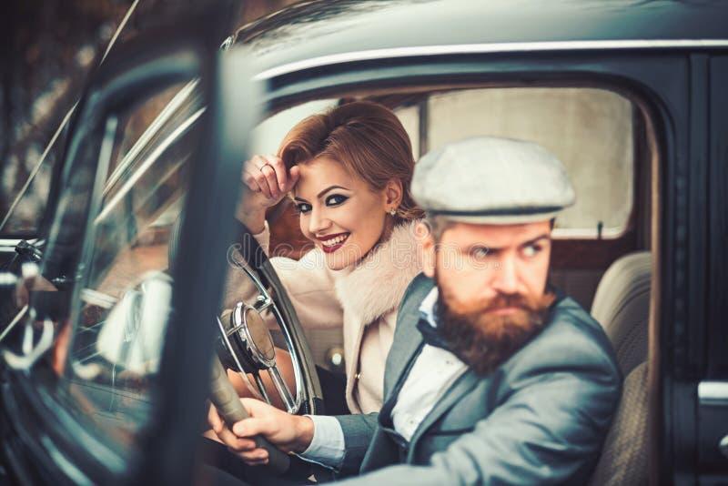 : eskortuje pojęcie z brodatym kierowcą i luksus dziewczyną w retro samochodzie obraz stock