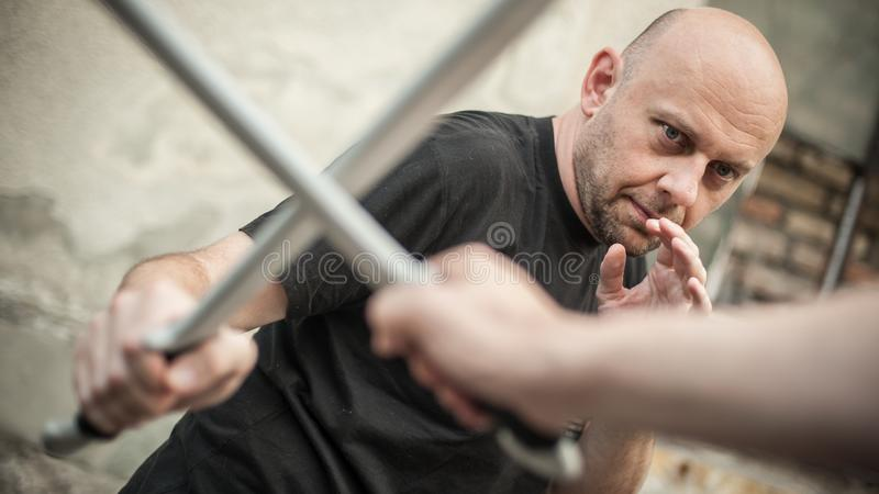 Eskrima and kapap instructor demonstrates machete weapon fighting technique royalty free stock photography