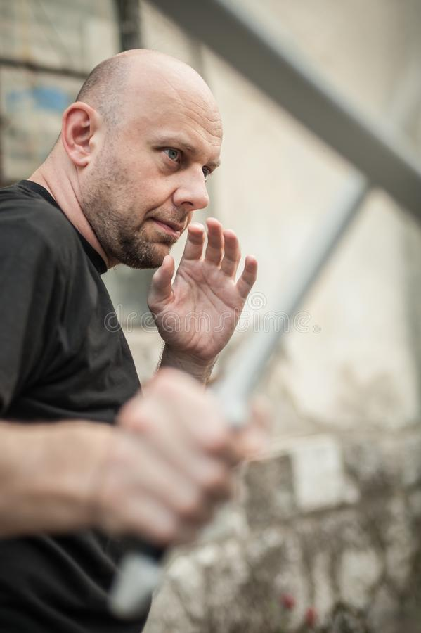Eskrima and kapap instructor demonstrates machete weapon fighting technique royalty free stock photo