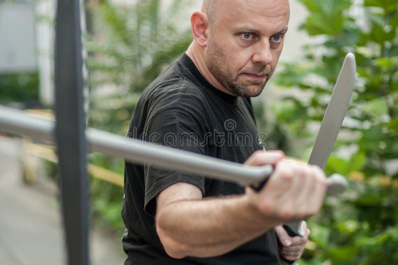 Eskrima y el instructor del kapap demuestra técnica que lucha del arma del machete fotos de archivo libres de regalías