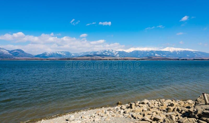 Eslovaquia: Lago Liptovska Mara con las montañas del tatra en el fondo Montañas del invierno, nubes imagen de archivo libre de regalías