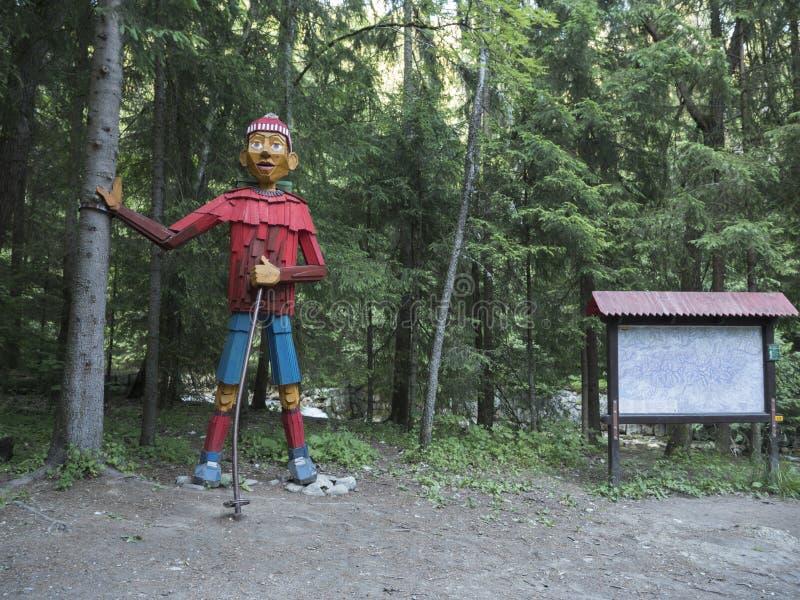Eslovaquia, Tatra Occidental, 3 de julio de 2019: gran estatua de madera colorida tallada de hiker al principio de Uzka fotos de archivo