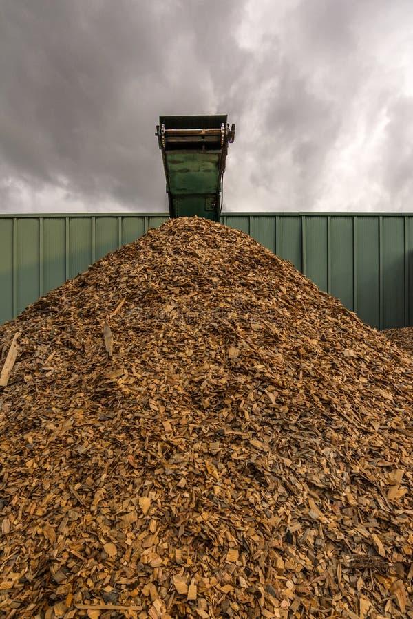 Esmagar a máquina da madeira e dos logs ao desperdício de processo e transforma em pelotas imagens de stock royalty free