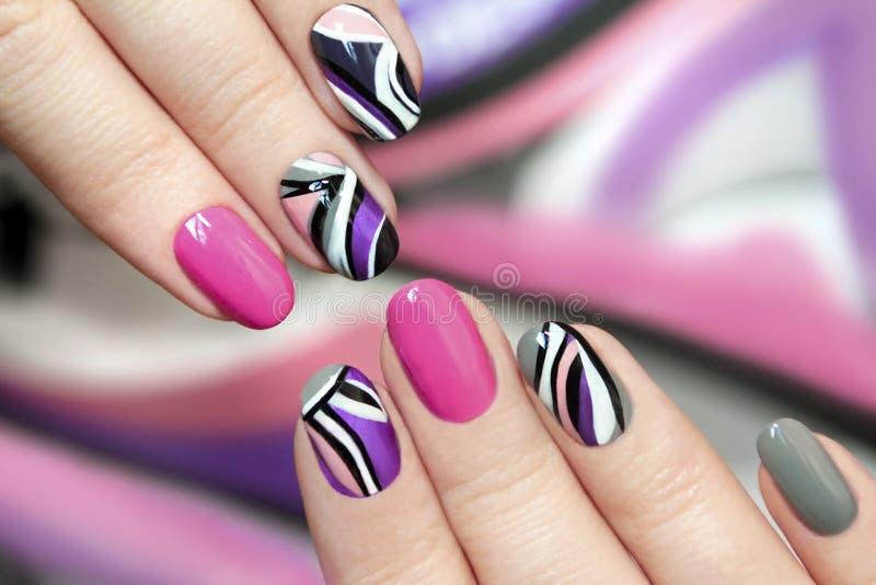 Esmalte de uñas púrpura rosado de moda fotografía de archivo