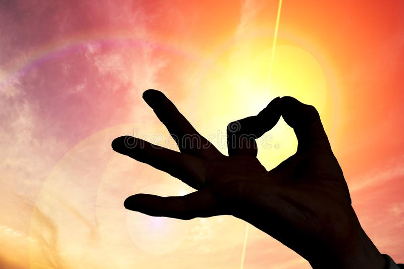 Esotericism and meditation concept. Silhouette of hand in sunset royalty free stock photos