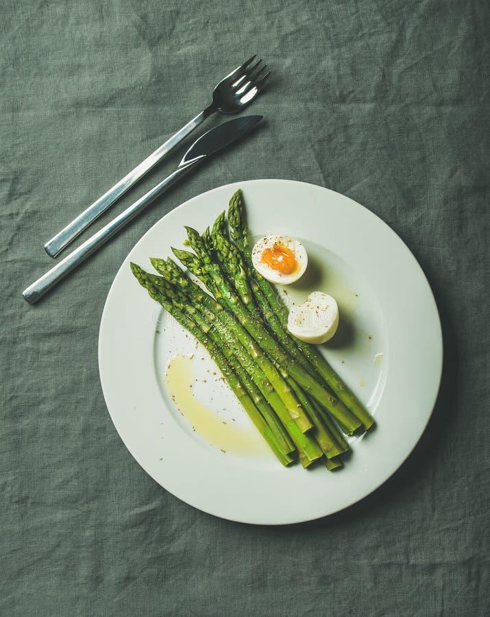 Espárrago cocinado con el huevo pasado por agua y las hierbas en la placa blanca imagen de archivo