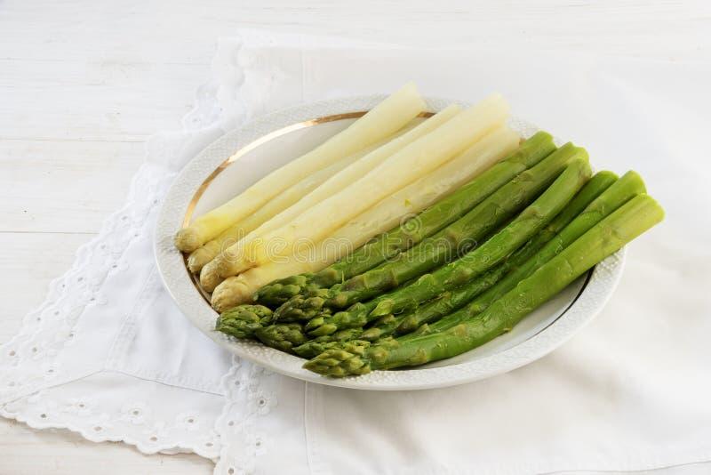 Espárrago cocinado, verde y blanco en una placa, tabla blanca con n fotografía de archivo