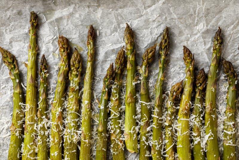 Espárrago verde asado a la parrilla asperjado con el queso parmesano rallado en el papel de pergamino blanco, visión superior fotos de archivo