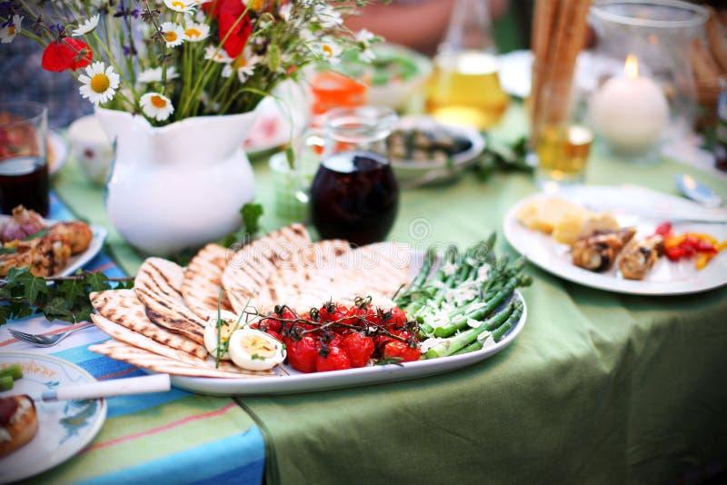 Espárrago y tomates asados a la parrilla con el pan Pita en la mesa de picnic fotos de archivo libres de regalías