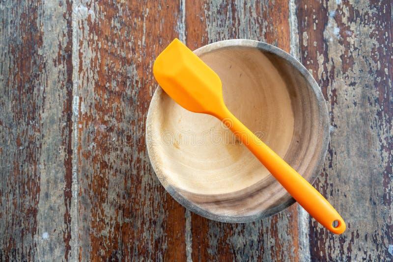 Espátula alaranjada do silicone com a bacia de madeira na tabela de madeira fotografia de stock