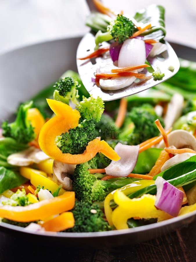 Espátula que agita vegetais em um frigideira chinesa da fritada da agitação. foto de stock