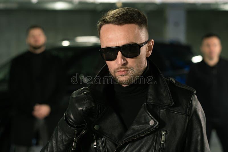 Espía o gángster masculino con gafas de sol, guantes de cuero negro y chaqueta imagen de archivo