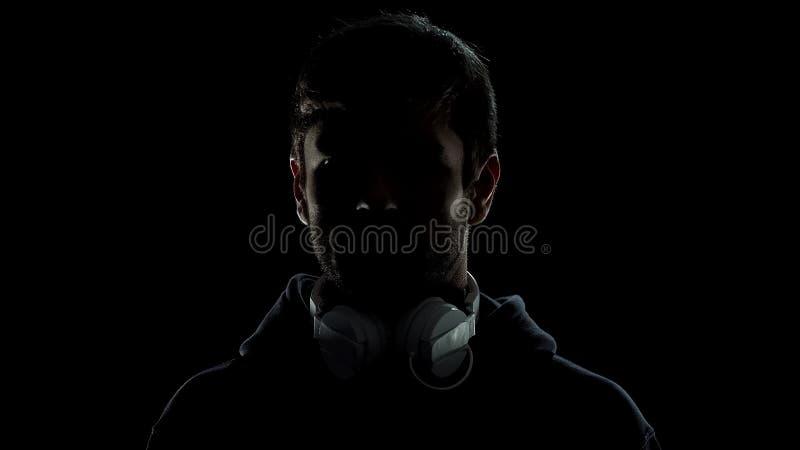 Espía peligroso con los auriculares, ataque ilegal de la aislamiento, salida de datos del servidor fotografía de archivo