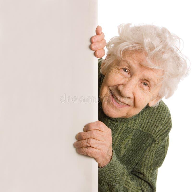 Espías de la mujer mayor aislados en el fondo blanco imagen de archivo libre de regalías