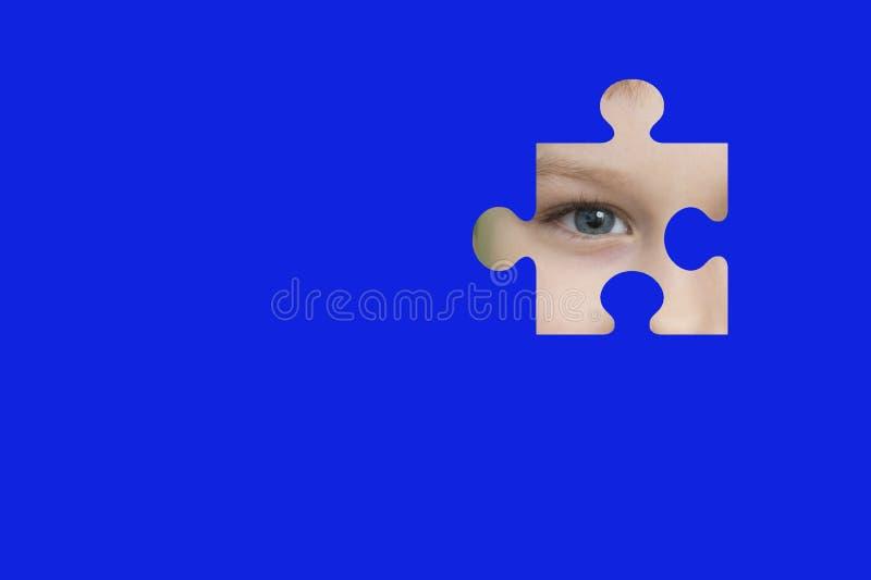 Espías del niño con un rompecabezas azul Símbolo de la conciencia del autismo imagenes de archivo