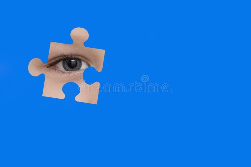 Espías del niño con un rompecabezas azul Símbolo de la conciencia del autismo fotos de archivo