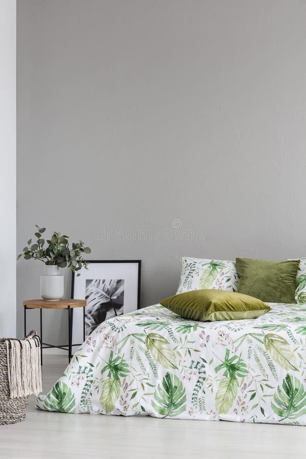 Espaço da cópia na parede cinzenta do quarto acolhedor com teste padrão da folha nos descansos do fundamento e do verde azeitona imagem de stock