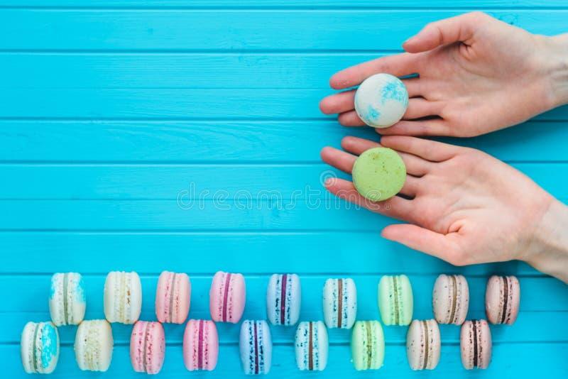 Espaço da cópia - o bolinho de amêndoa ou o macaron encontram-se nas mãos de uma menina em um fundo de madeira de turquesa Oferta imagem de stock royalty free