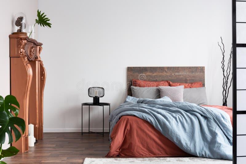 Espaço de cópia na parede branca vazia do interior do quarto russo com cama de tamanho rei com camas laranja e azul pastel foto de stock