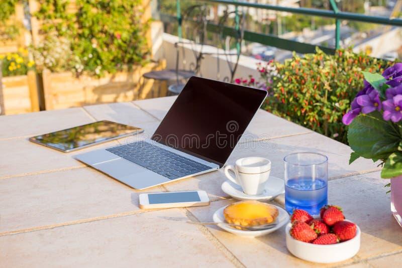 Espaço de funcionamento inspirador fora com portátil, tabuleta e telefone celular imagem de stock royalty free