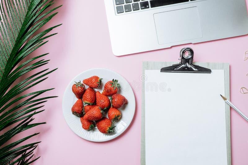 Espaço de funcionamento: Portátil, folha de palmeira, café e morango em um pino imagens de stock royalty free