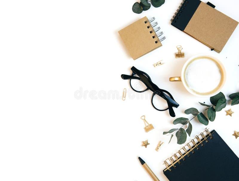 Espaço de trabalho branco da mesa de escritório com café, placa de papel, folhas do verde e materiais de escritório imagens de stock royalty free