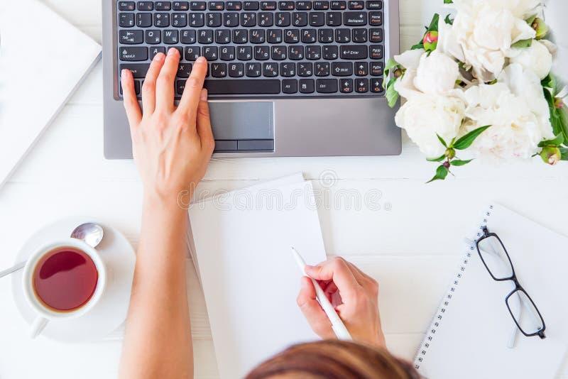 Espaço de trabalho com mão do ` s da menina no teclado e na escrita do portátil no caderno com placa vazia, copo do chá, vidros,  foto de stock royalty free