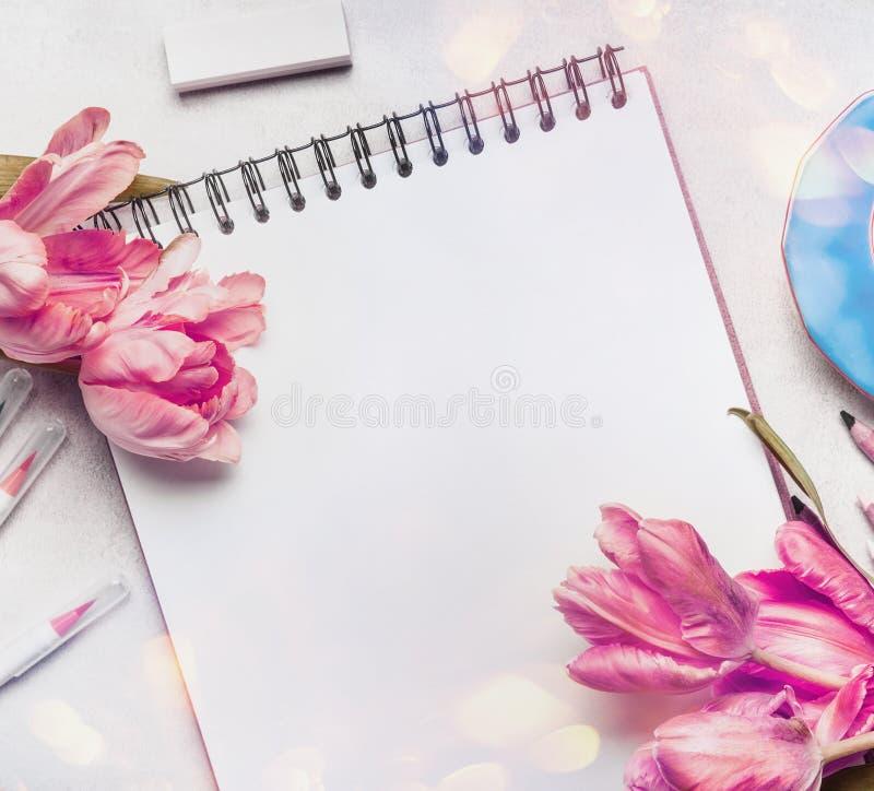 Espaço de trabalho da primavera das mulheres com pálido - tulipas cor-de-rosa, caderno ou bloco de desenho e marcadores coloridos foto de stock royalty free