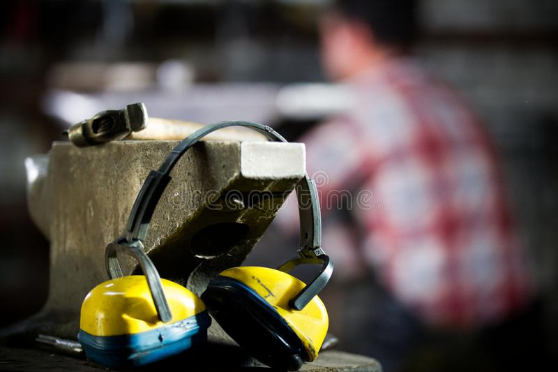 Espaço de trabalho do ferreiro o martelo, os fones de ouvido e as luvas encontram-se no batente imagem de stock royalty free