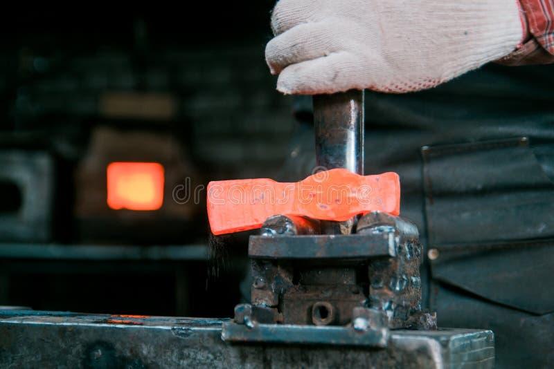 Espaço de trabalho do ferreiro Ferreiro que trabalha com metal encarnado do martelo novo no batente em uma forja Fazendo o furo imagem de stock