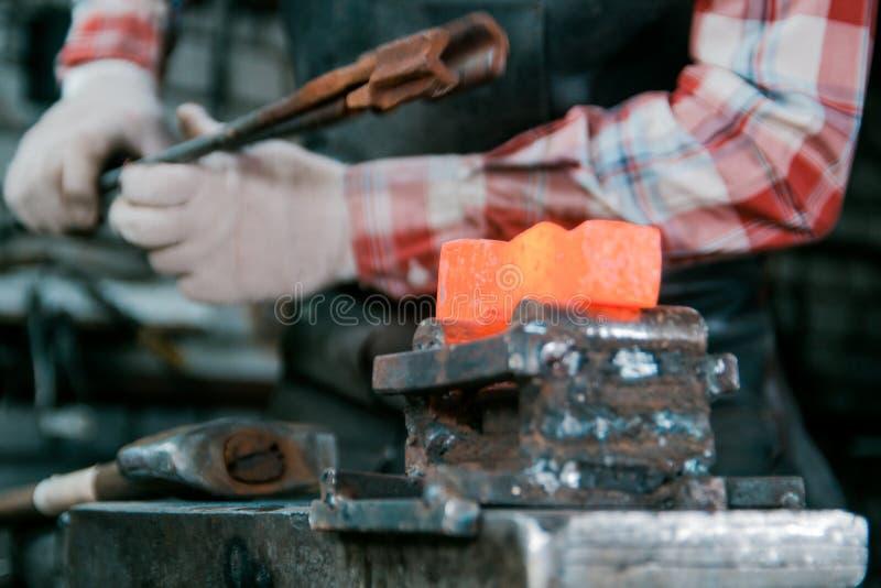 Espaço de trabalho do ferreiro Ferreiro que trabalha com o workpiece encarnado do metal do martelo novo no batente imagens de stock
