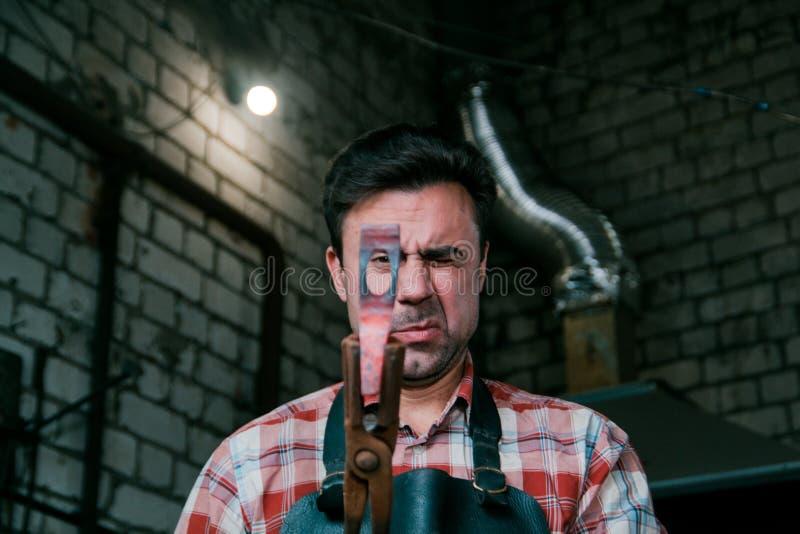 Espaço de trabalho do ferreiro Ferreiro que trabalha com o workpiece encarnado do metal do martelo novo no batente em uma forja V fotos de stock