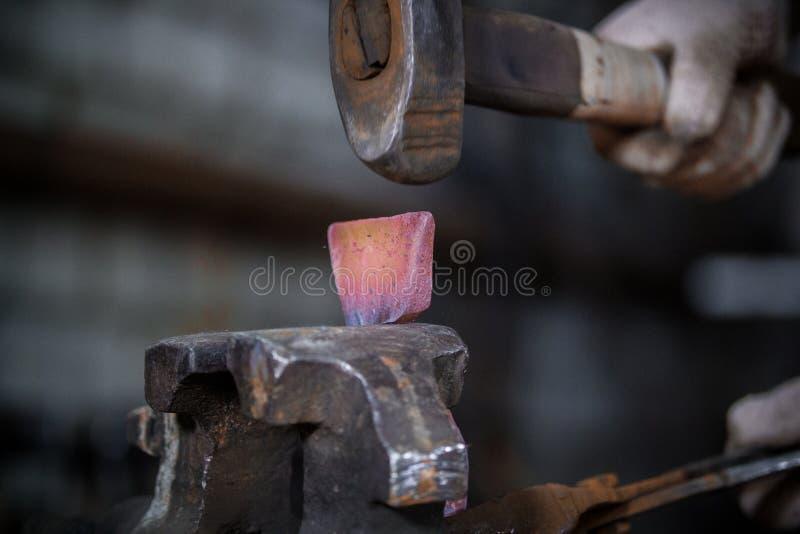Espaço de trabalho do ferreiro Ferreiro que trabalha com o workpiece encarnado do metal do martelo novo no torno na forja foto de stock royalty free