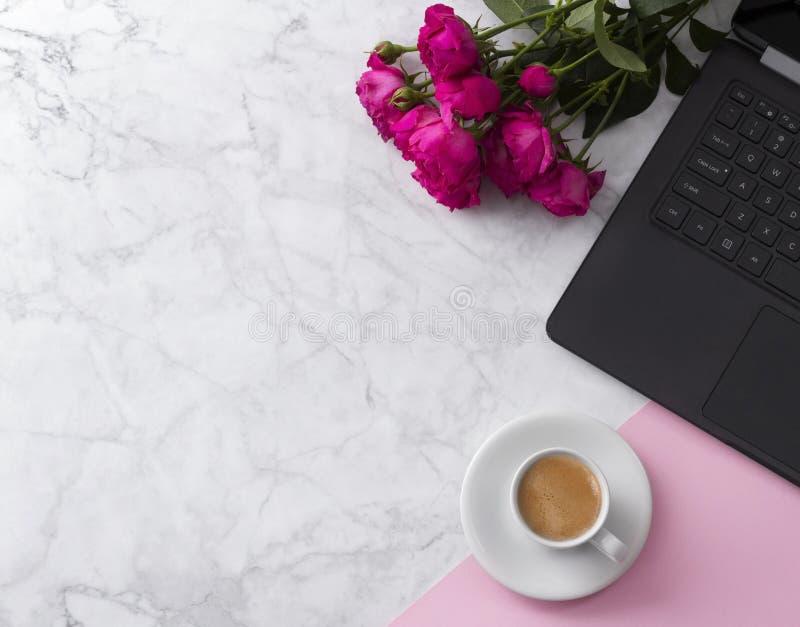 Espaço de trabalho feminino com laptop, ramalhete das rosas e café em uma tabela de mármore imagens de stock royalty free
