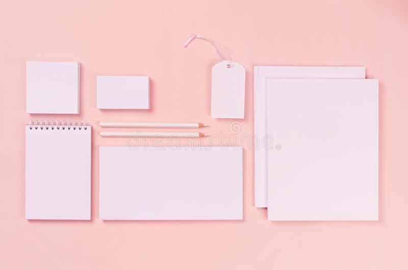 Espaço de trabalho minimalistic moderno com artigos de papelaria vazios brancos no fundo macio do rosa pastel, vista superior fotografia de stock