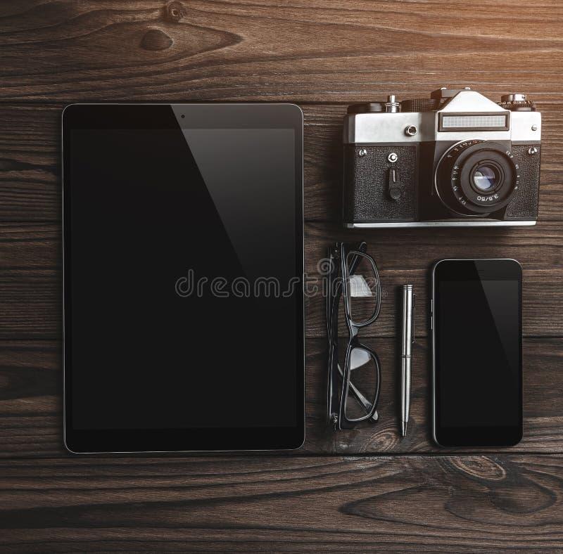 Espaço de trabalho para o fotógrafo Configuração lisa da tabuleta digital, câmera, telefone, vidros, lápis na tabela de madeira imagem de stock
