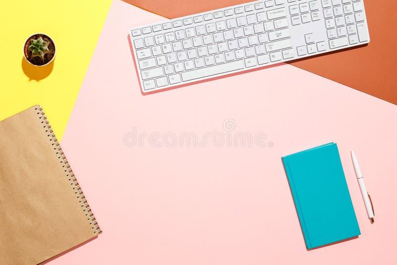 Espaço de trabalho positivo moderno Composição lisa da configuração do teclado, cacto, diário com a pena na mesa colorida Cor-de- imagens de stock royalty free