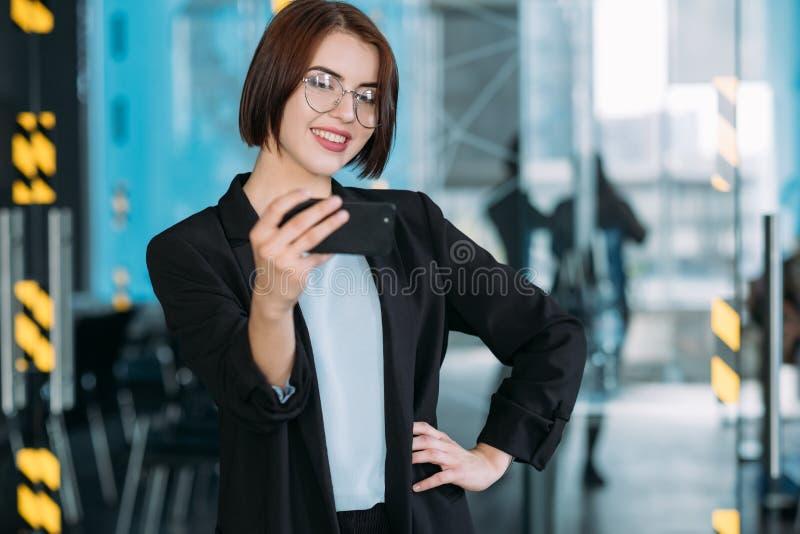 Espaço de trabalho de sorriso novo do interno da mulher de negócio imagem de stock royalty free