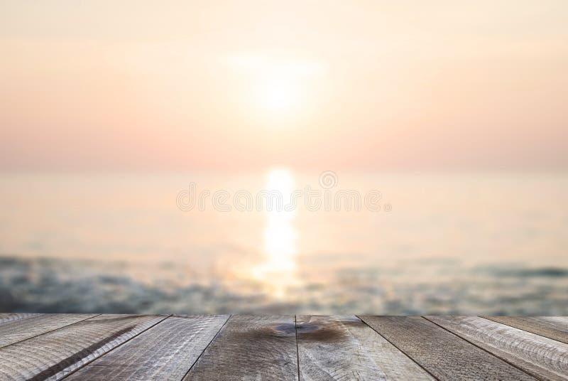 Espaço livre de madeira na tabela com a praia bonita do por do sol sobre o mar imagem de stock
